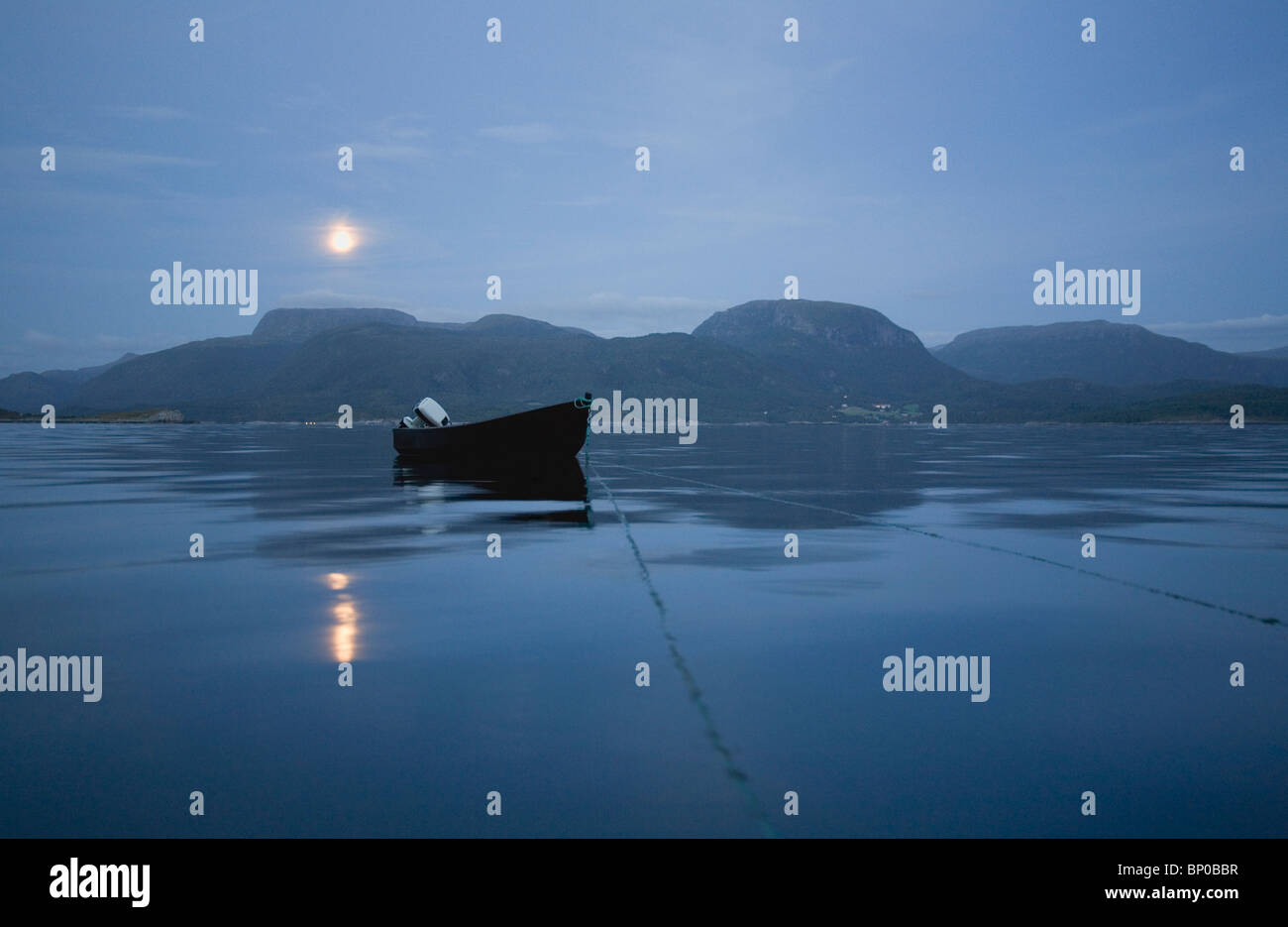 Wooden boat on calm sea at night - Stock Image