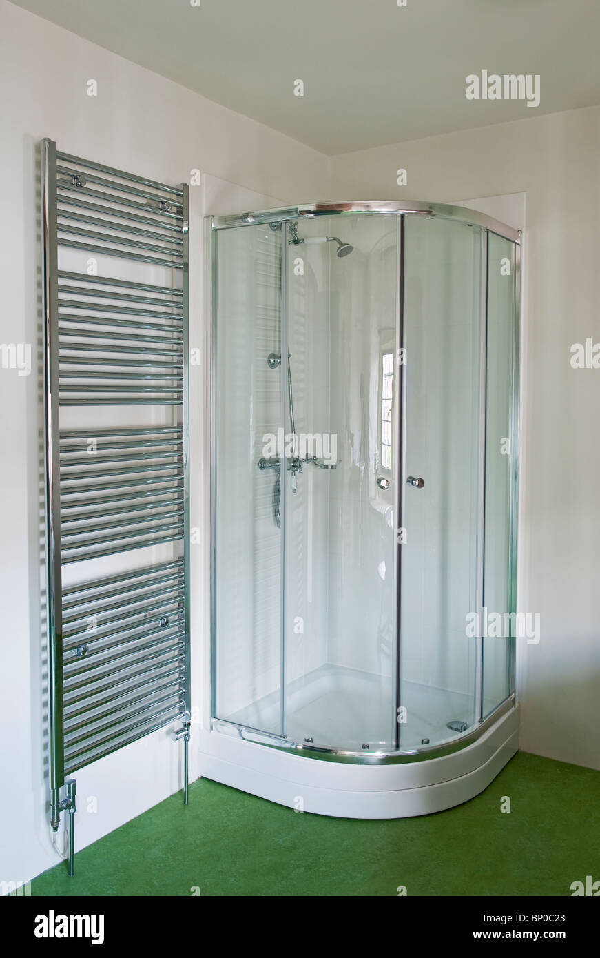 A heated towel rail and a corner shower unit in a modern bathroom ...