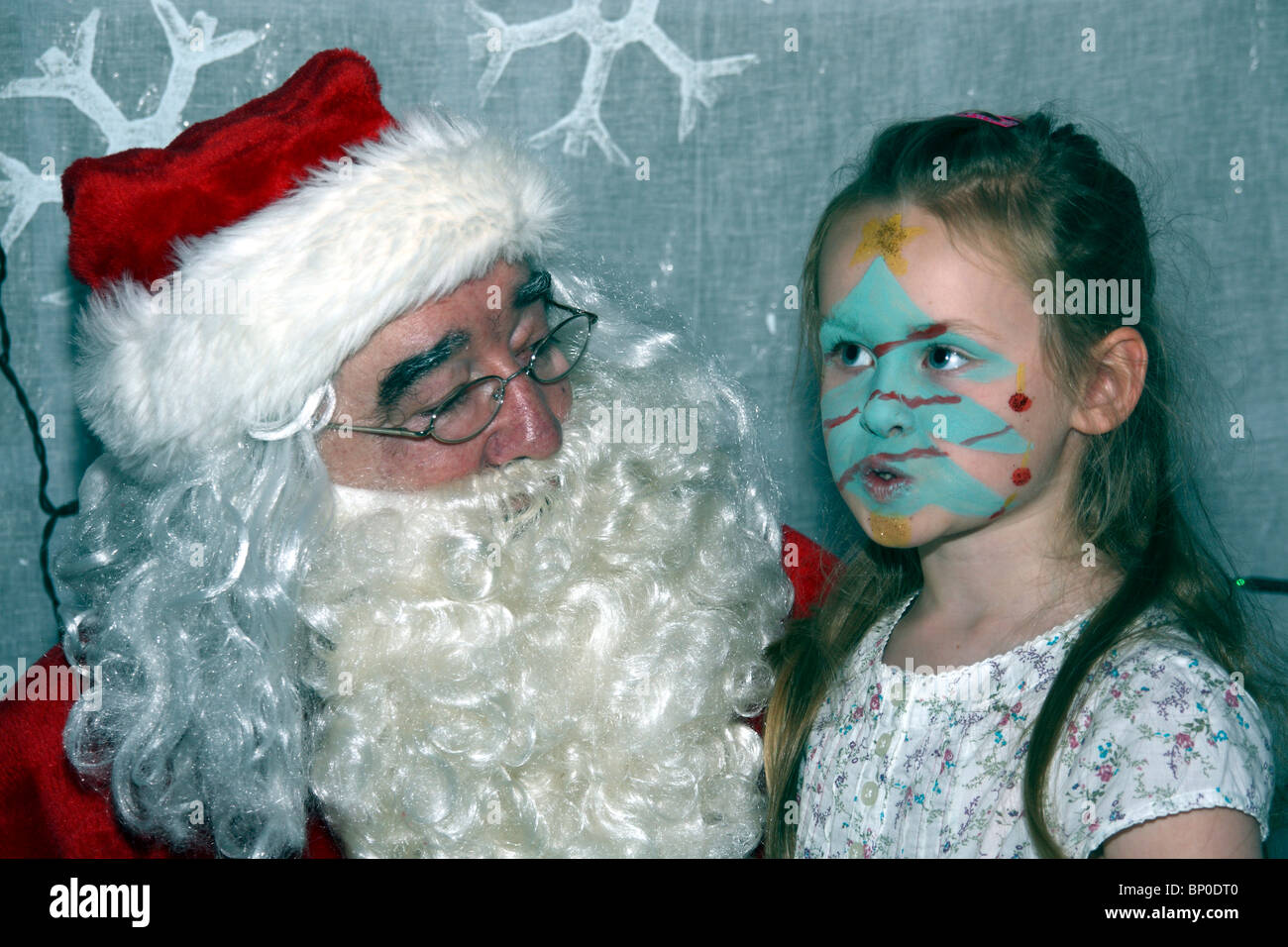 Little Girl With Christmas Tree Face Painting Meeting Santa Claus In Stock Photo Alamy
