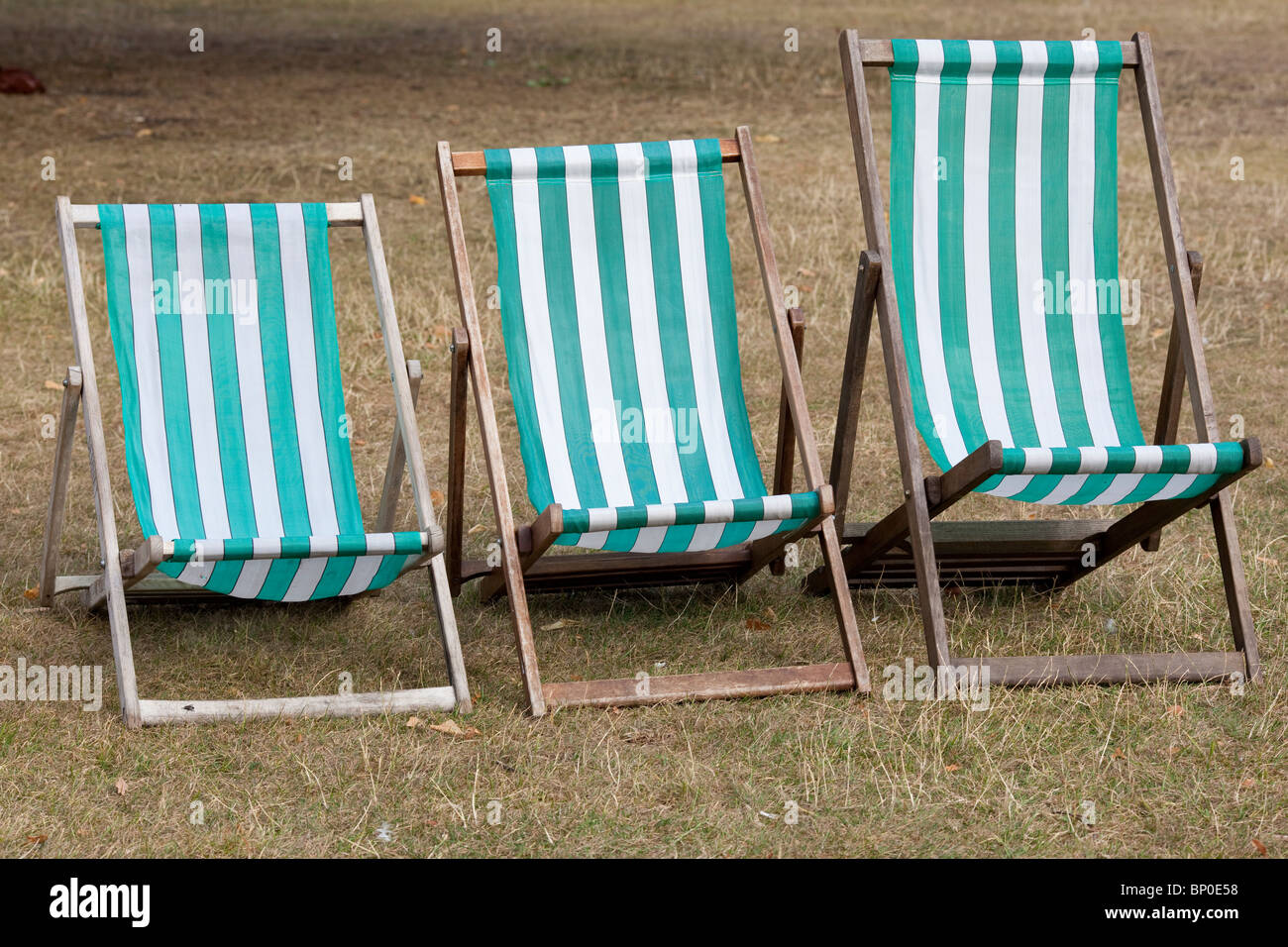 Three striped deck chairs in various sizes sit unused at St James Park, London. Photo:Jeff Gilbert - Stock Image