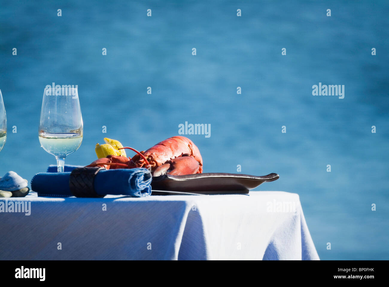 Laid table with lobster and white wine on seaside - Stock Image