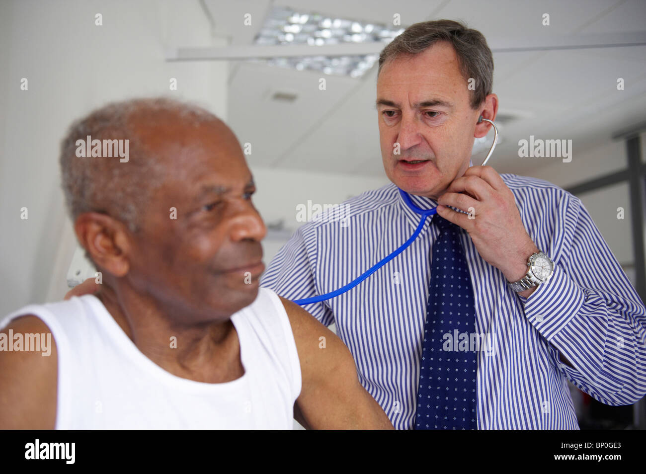Doctor with stethoscope with elderly man Stock Photo