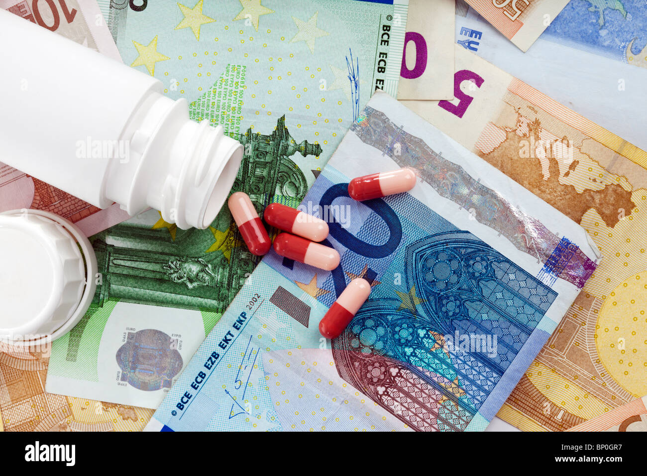 high cost of health care - medicine capsules falling from bottle onto european currency notes, view from above - Stock Image