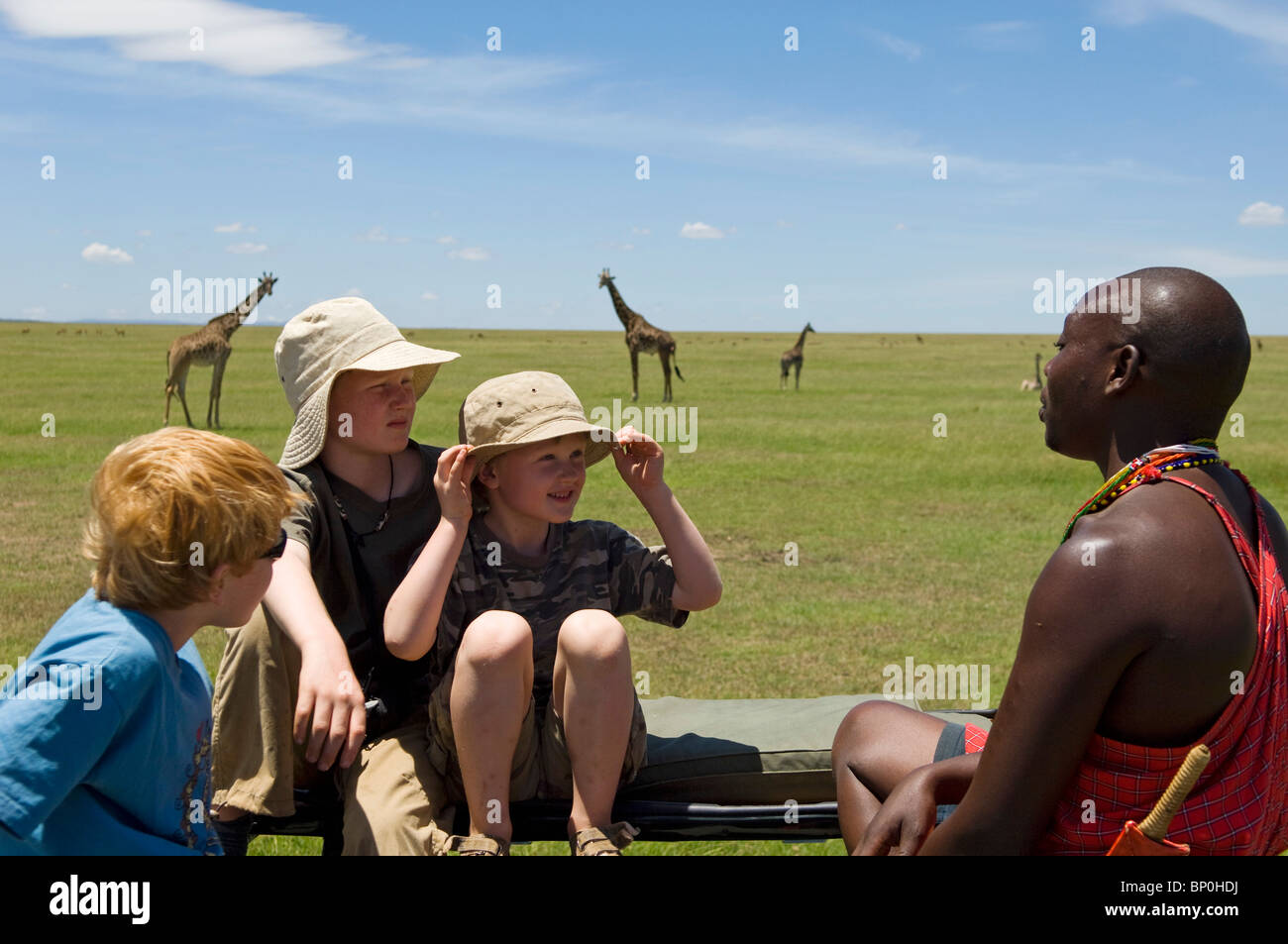 Kenya, Masai Mara. Safari guide, Salaash Ole talks to boys on safari during a game drive out on the plains. (MR) - Stock Image