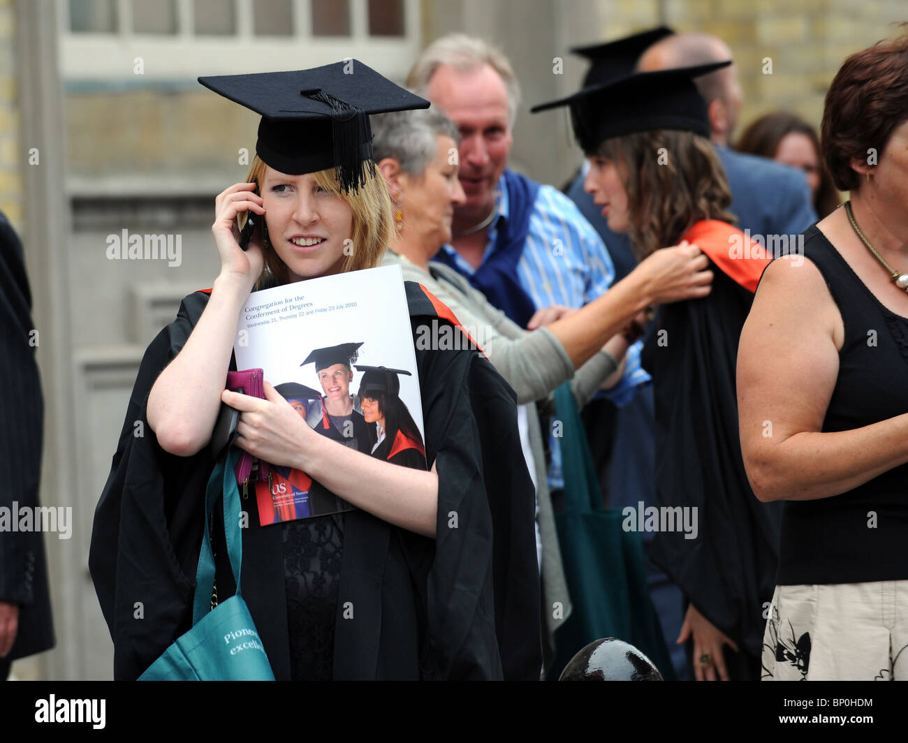 A University of Sussex graduate phones a friend before heading inside Brighton Dome for her graduation ceremony - Stock Image