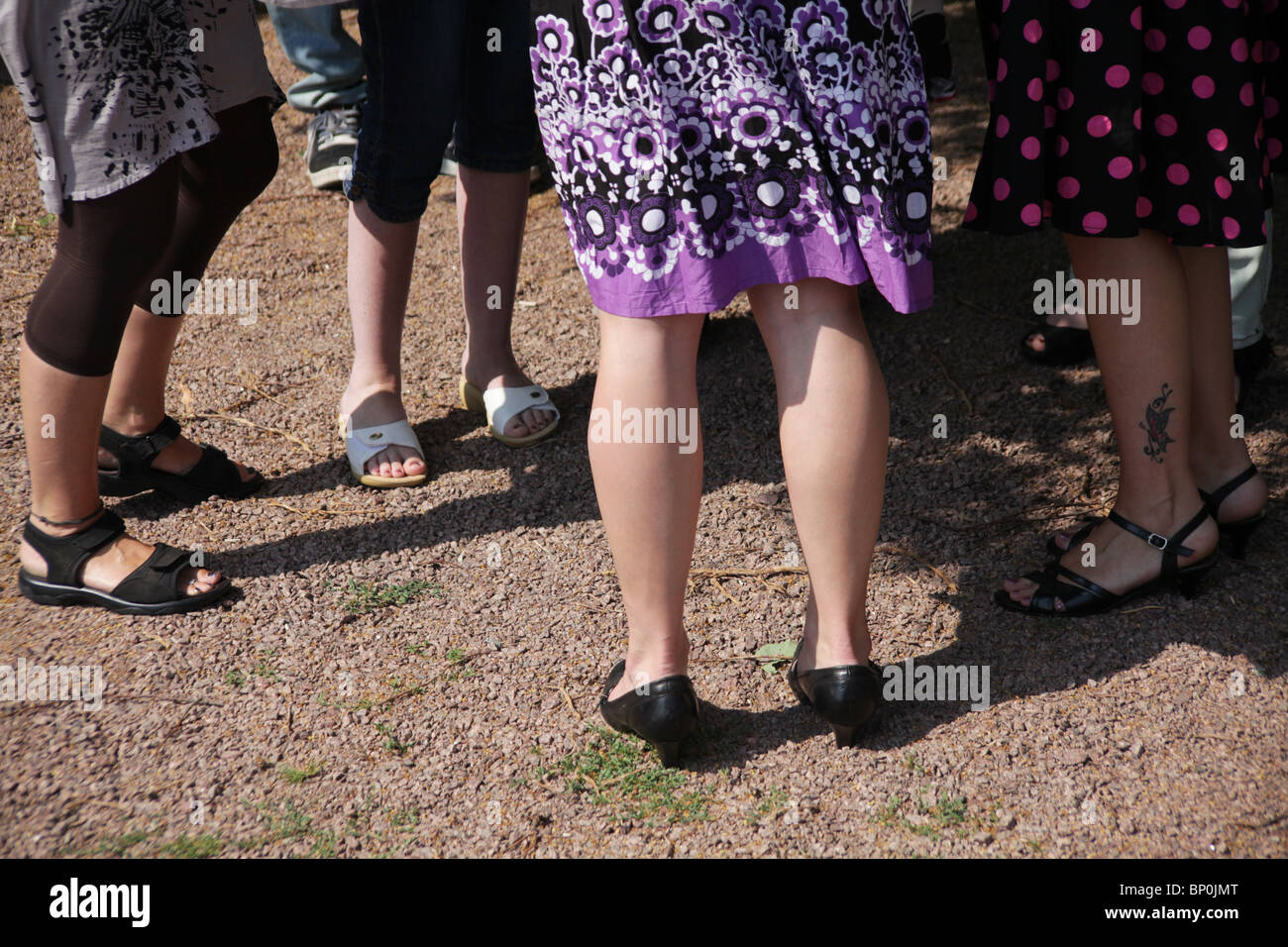 Women standing at a garden party ankle tattoo Stock Photo
