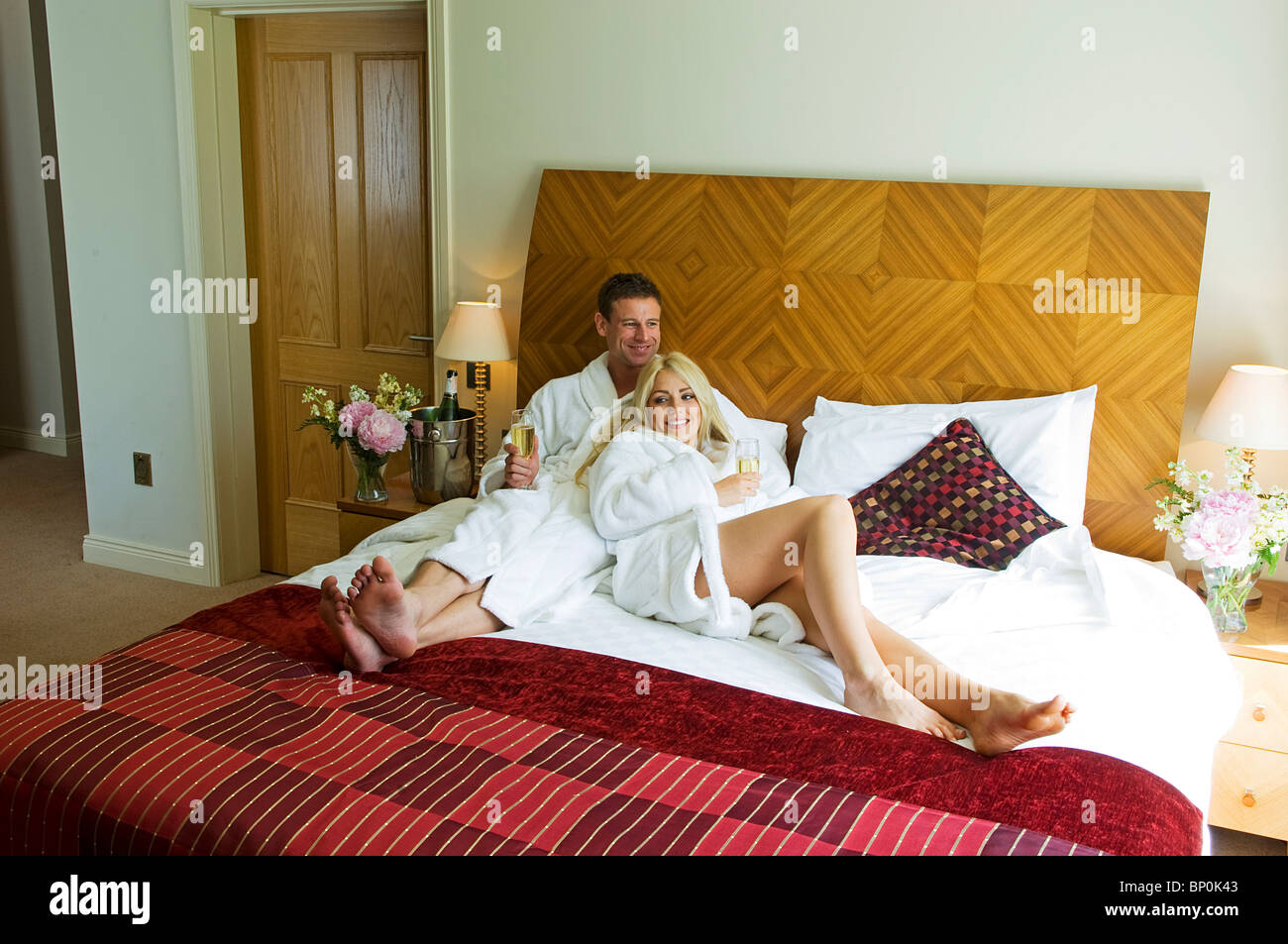 Northern Ireland, Fermanagh, Enniskillen. Couple relax with a glass of champagne in their bedroom at the Killyhevlin - Stock Image