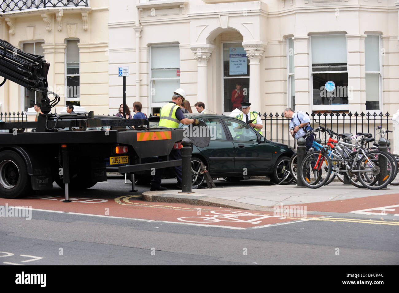 A Traffic warden supervises the removal of an illegally parked car from a disabled bay in Brighton - Stock Image