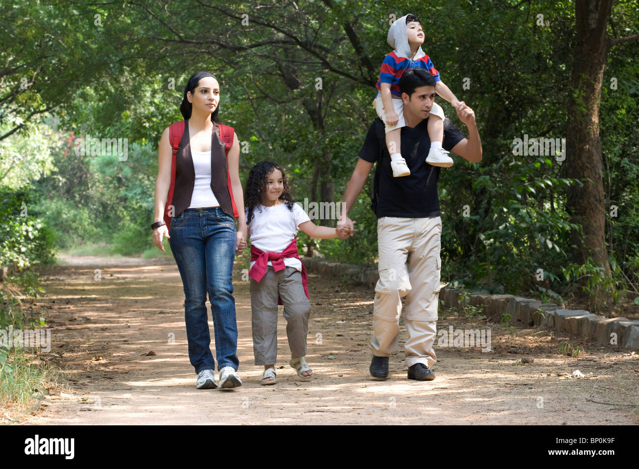Family going for a walk in a park - Stock Image