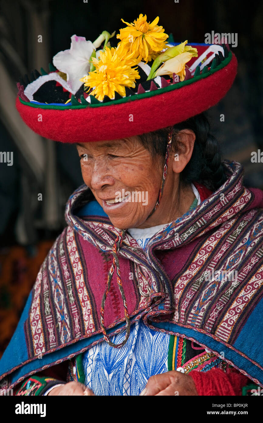 Peru, An old woman in traditional Indian costume with her round, saucer-shaped hat decorated with fresh flowers. - Stock Image