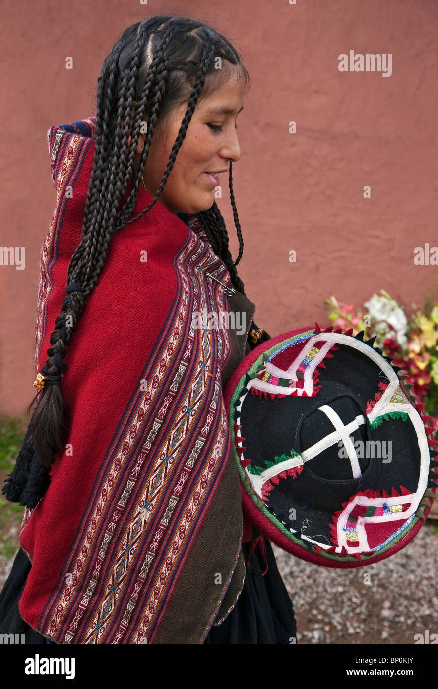 Peru, A young woman in traditional Indian costume with long braided hair. - Stock Image