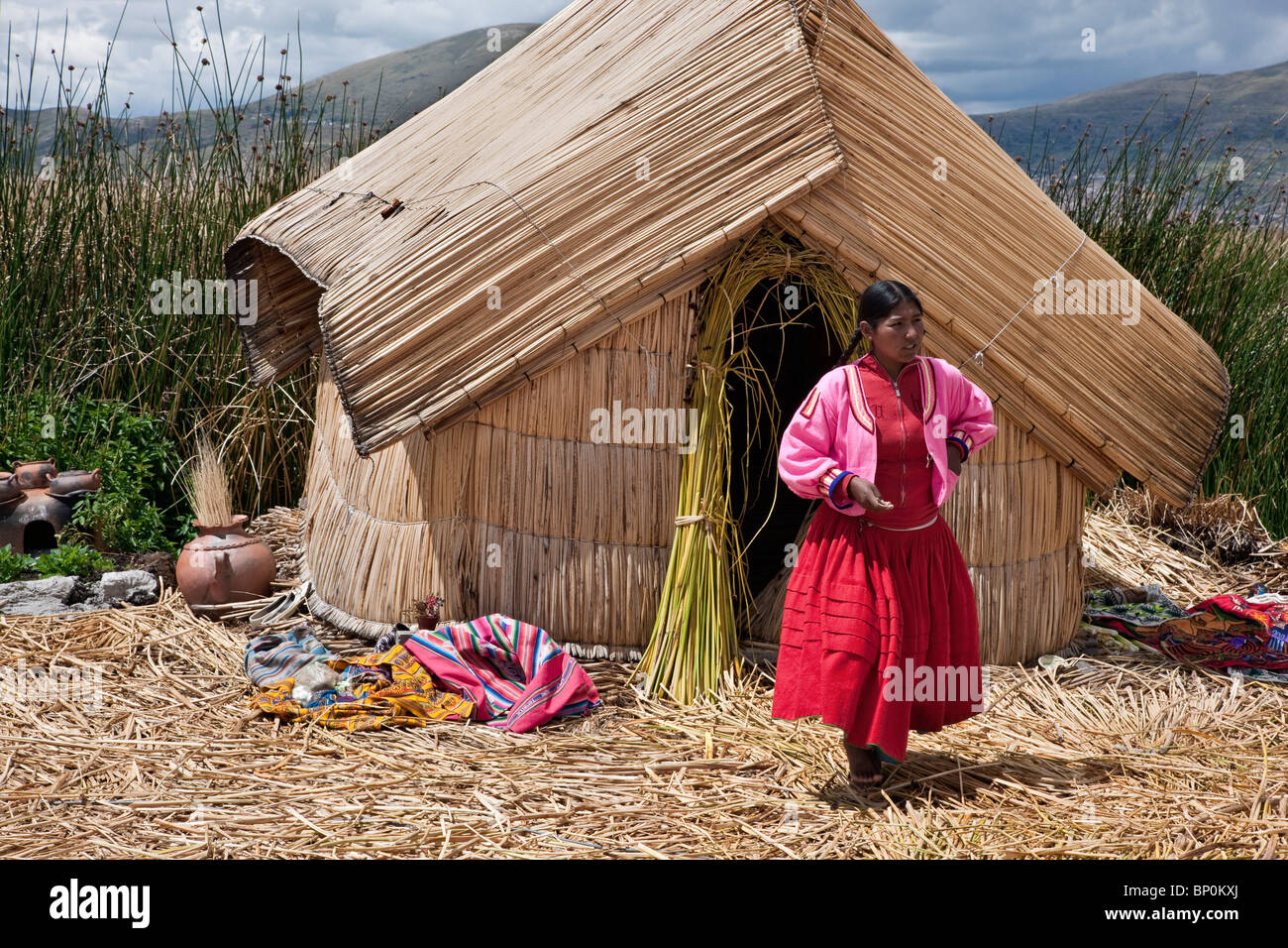Peru, A girl from Uros outside her reed home on one of the unique floating islands of Lake Titicaca. - Stock Image