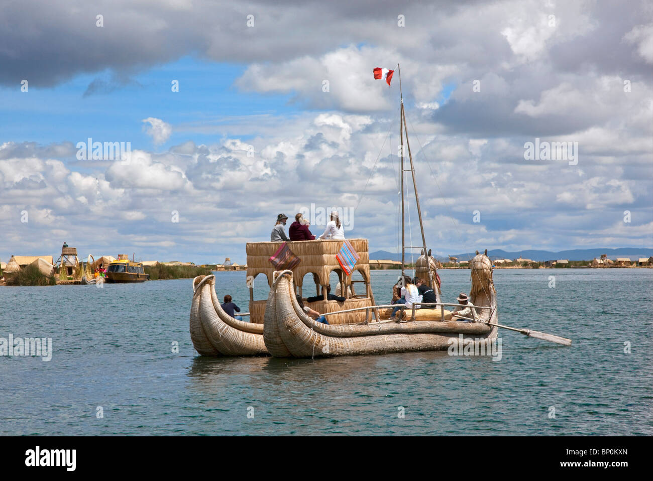 Peru, A large reed boat is rowed down the main channel between the unique floating islands of Uros on Lake Titicaca. - Stock Image