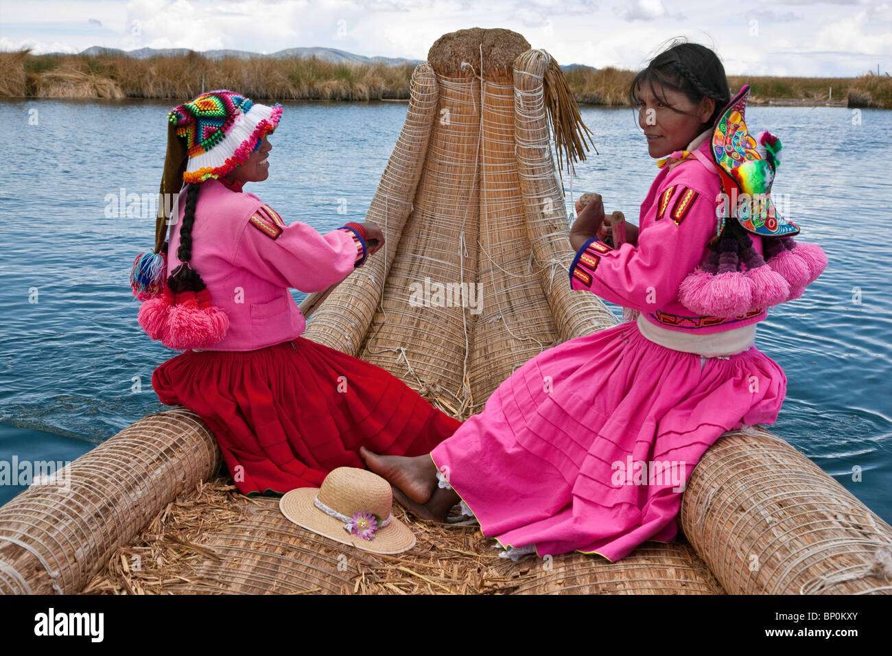 Peru, two girls from Uros row a reed boat to one of the unique floating islands of Lake Titicaca. - Stock Image