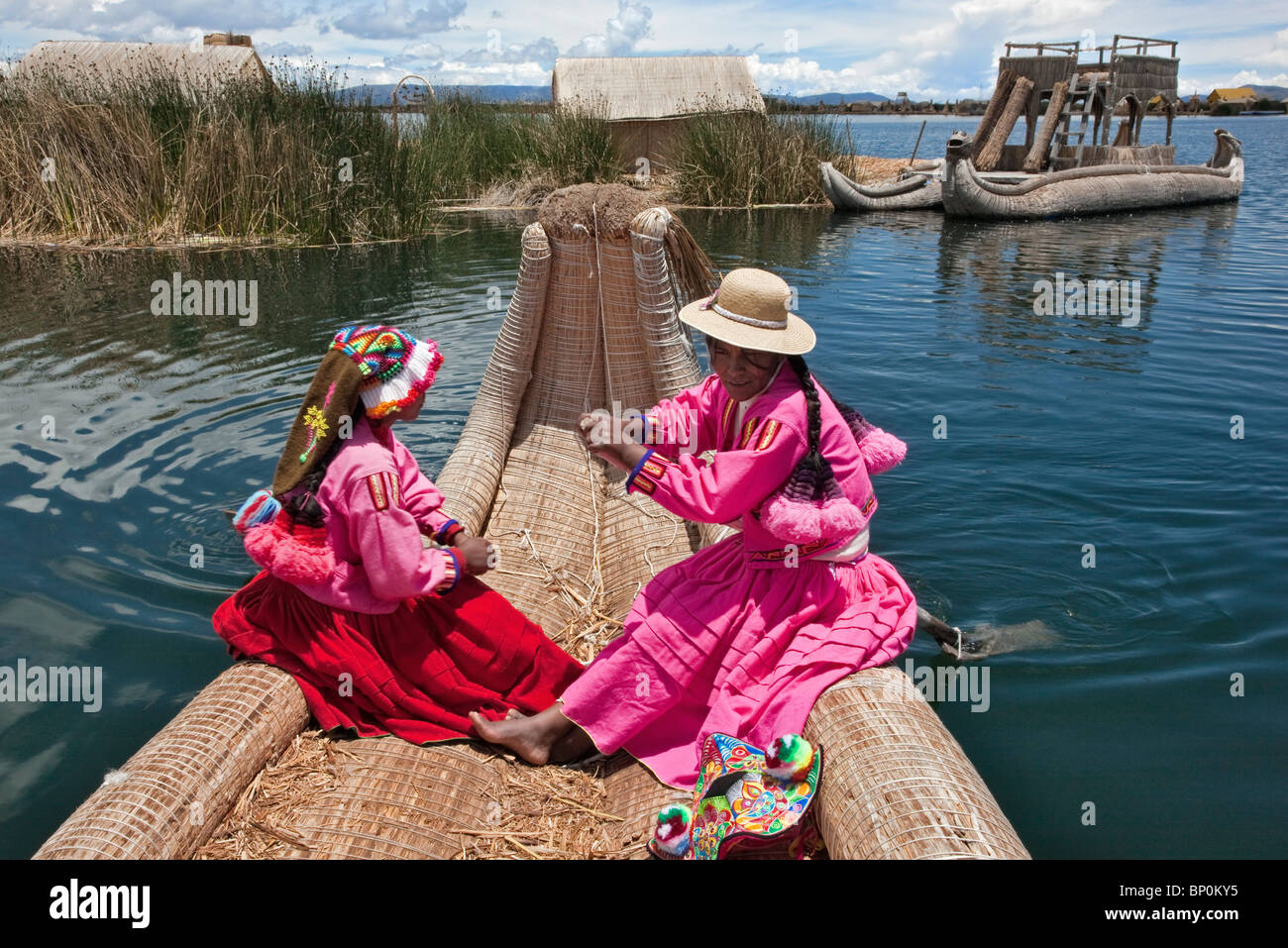 Peru, Two girl from Uros row a reed boat to one of the unique floating islands of Lake Titicaca. - Stock Image