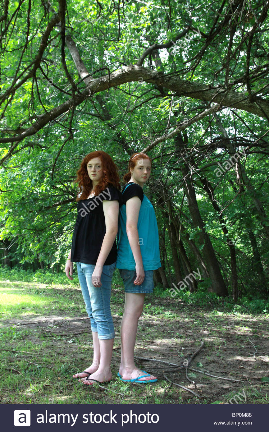 Identical twin teenage girls with red hair standing back to back. - Stock Image