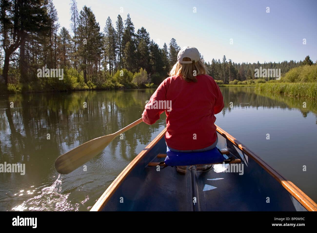 A woman paddling a canoe on the Deschutes River, Oregon - Stock Image