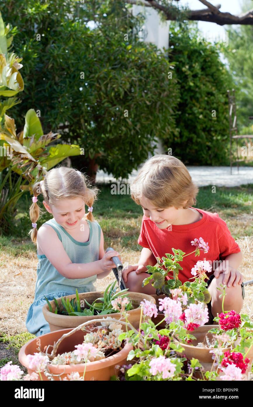 Children watering flowers - Stock Image