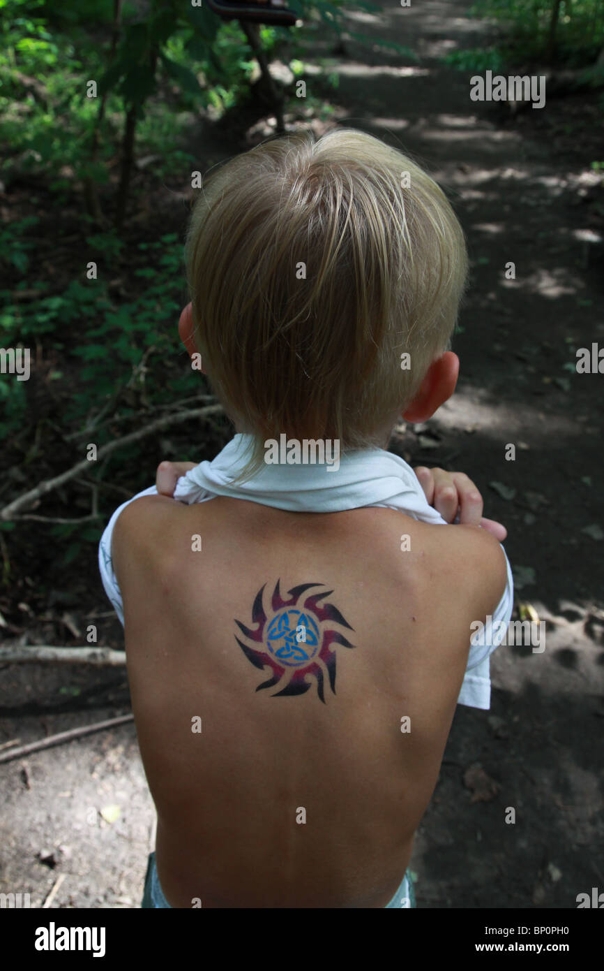 A 7 Year Old Boy Showing Off The Temporary Tattoo On His Back Stock