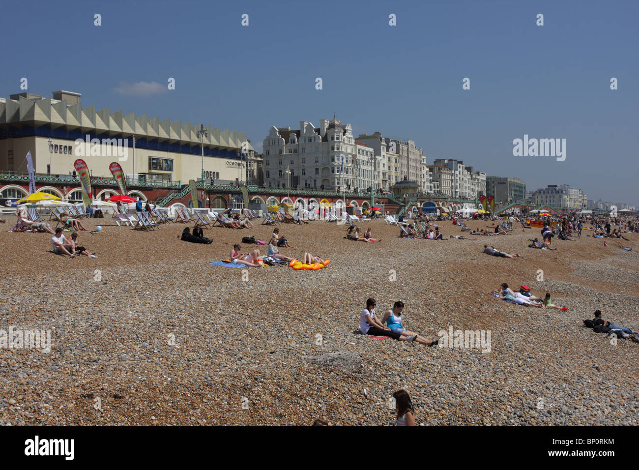 Bank Holiday tourists and locals enjoying beautiful weather on Brighton beach. Stock Photo