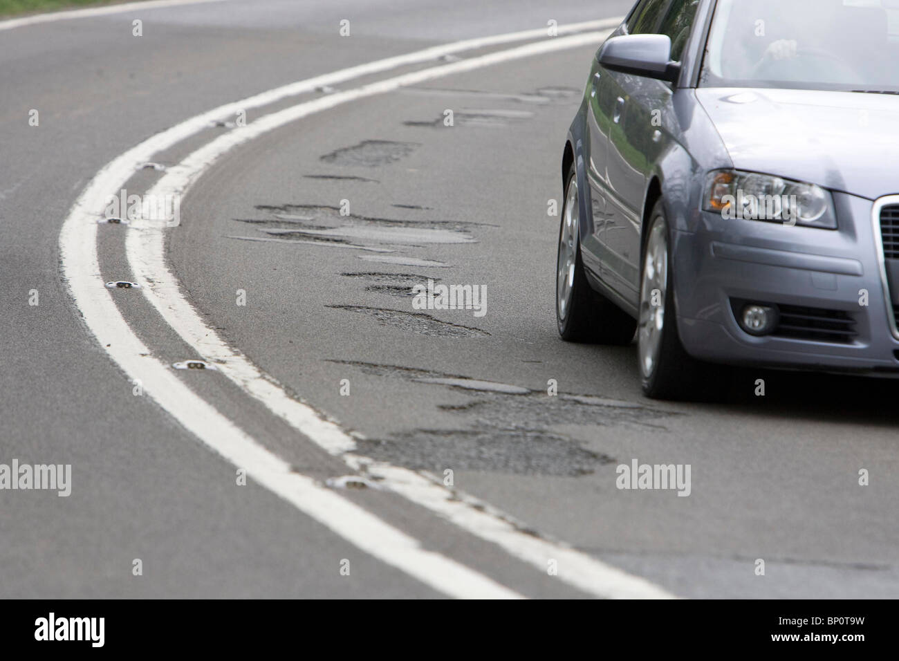 A motorist drives past a number of potholes on a country road. Picture by James Boardman. - Stock Image