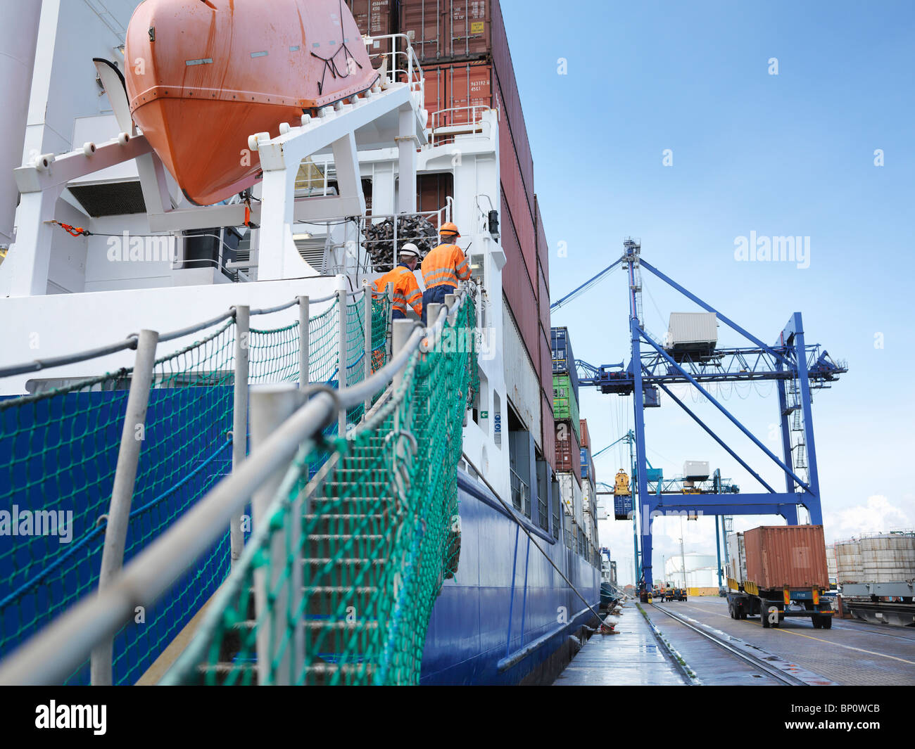 Sailors watching container ship loading - Stock Image