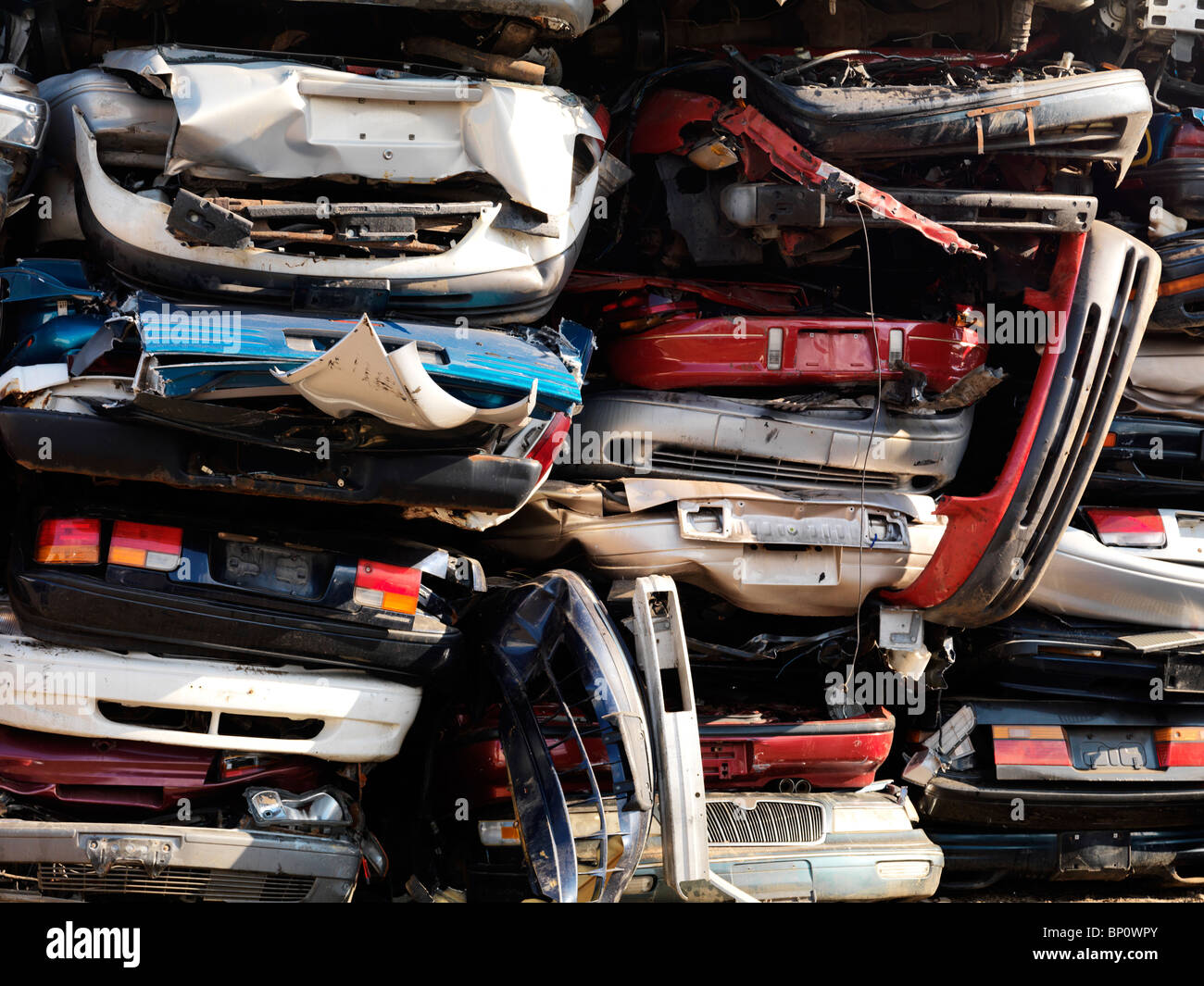 Piled up crushed cars on a scrap yard - Stock Image