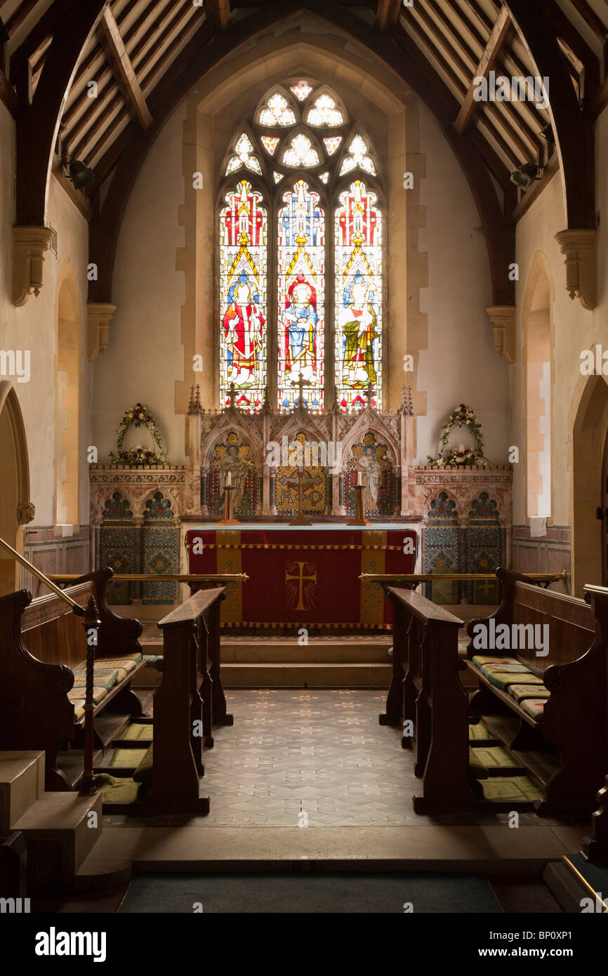 Inside view of an english village church looking up the knave towards the alter with a stained glass window - Stock Image
