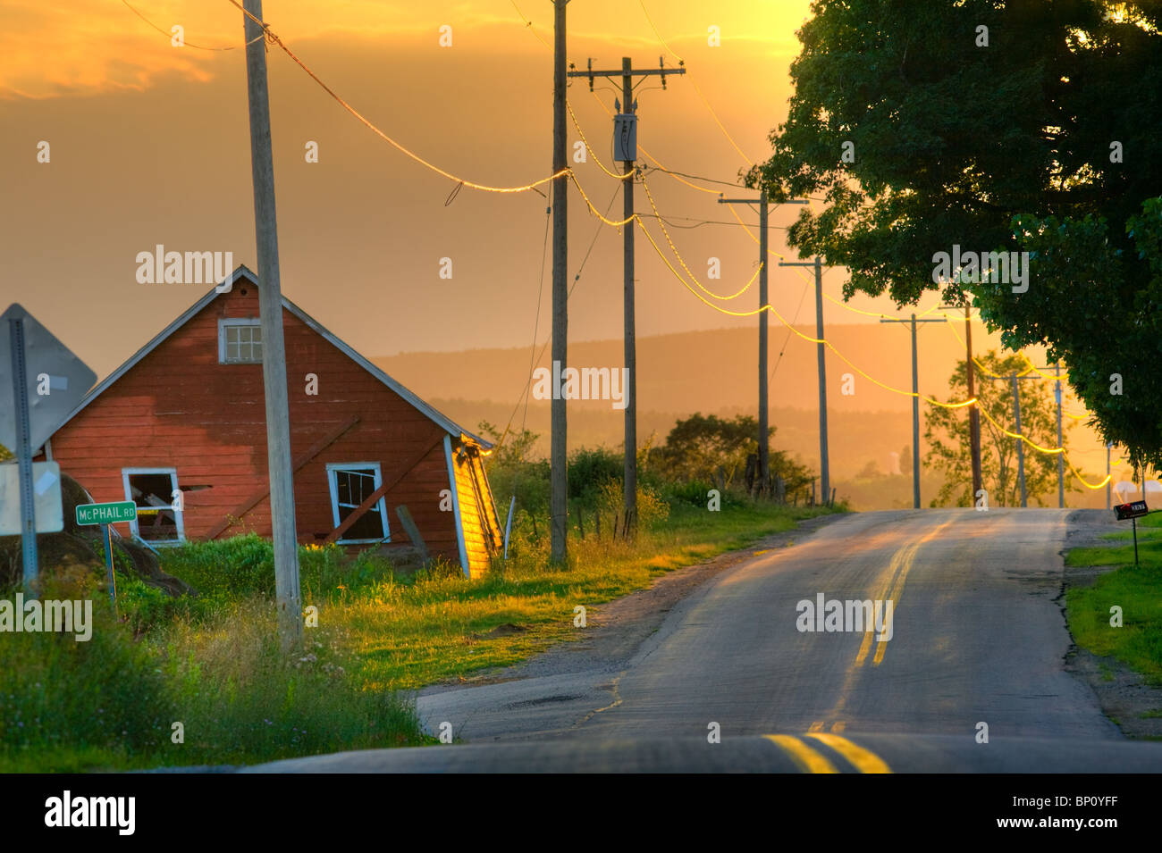 Golden sunset country road, leaning barn, upstate New York - Stock Image