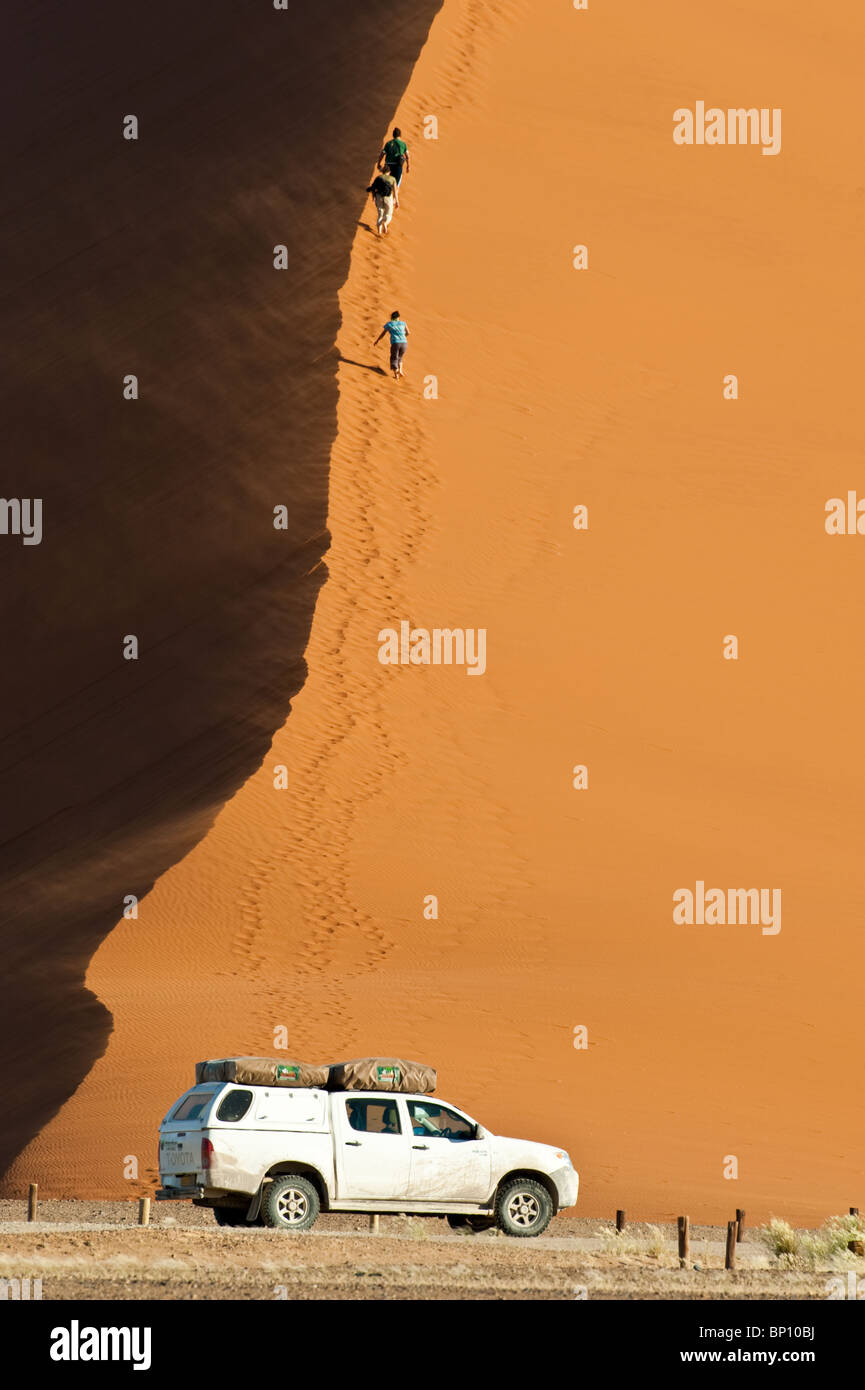 Tourists ascending dune 45 at Sossusvlei in Naukluft Park Central Namib desert Namibia Stock Photo