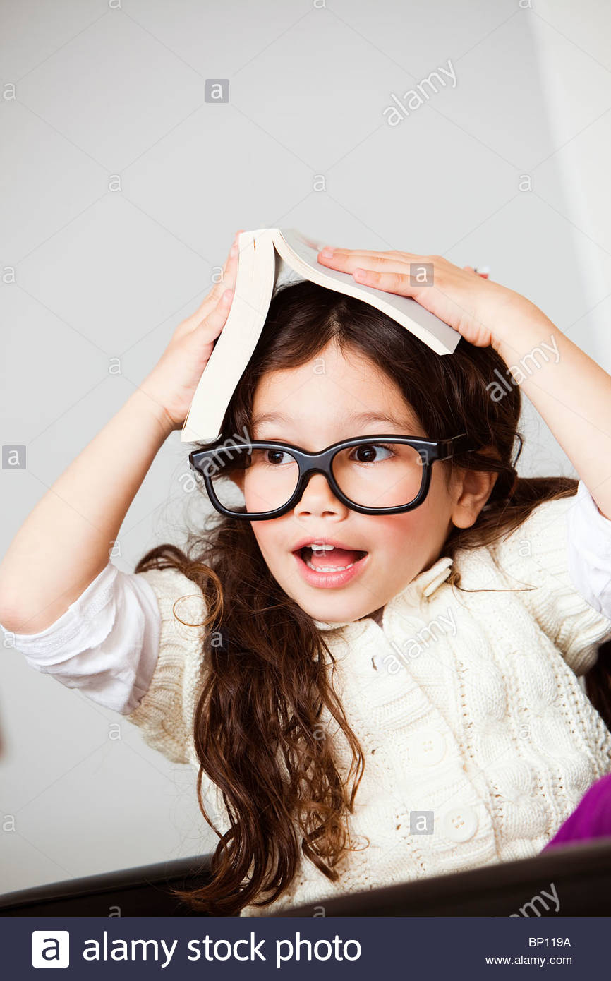 Astonished girl with book on her head - Stock Image