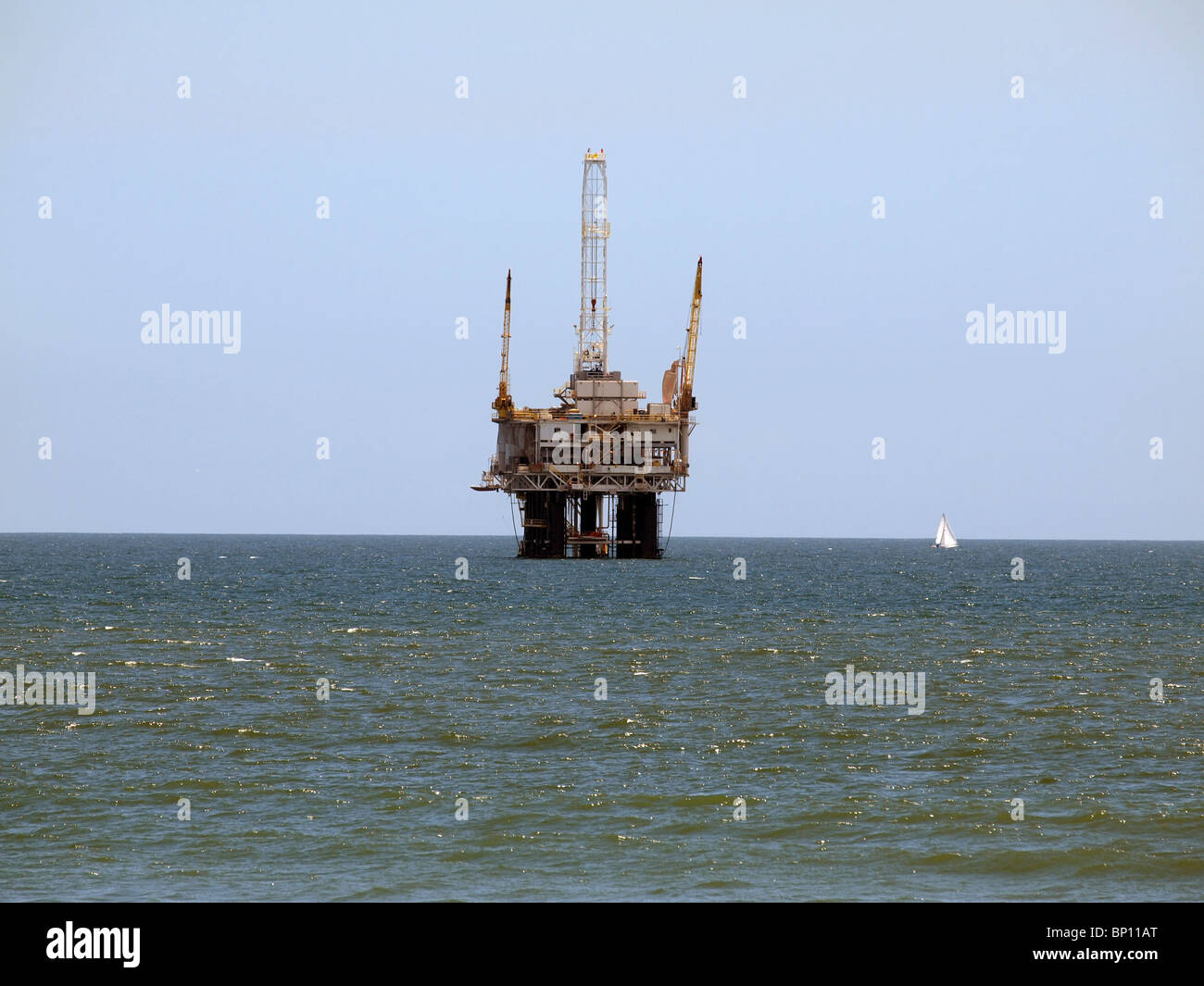 A sail boat passes a large offshore oil rig. - Stock Image