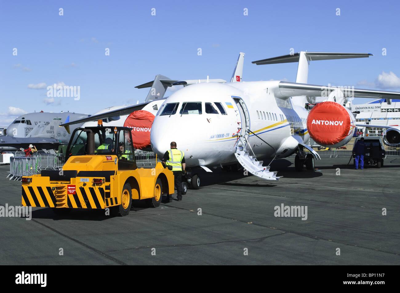 Antonov An-158 awaiting tow by a Hallam Terrier HE aircraft tug at Farnborough Airshow - Stock Image