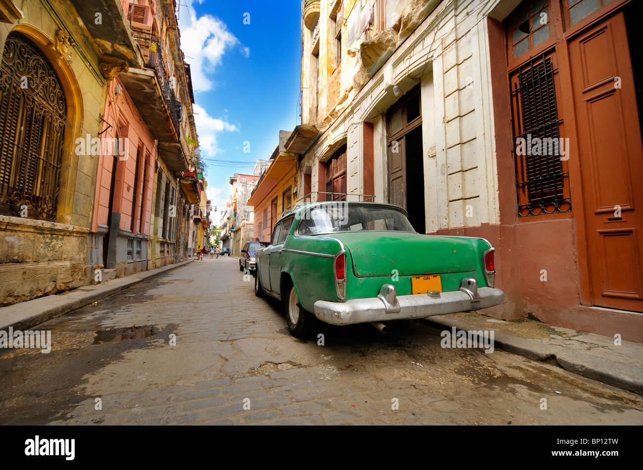 Vintage car parked in shabby Old Havana street with crumbling facades - Stock Image