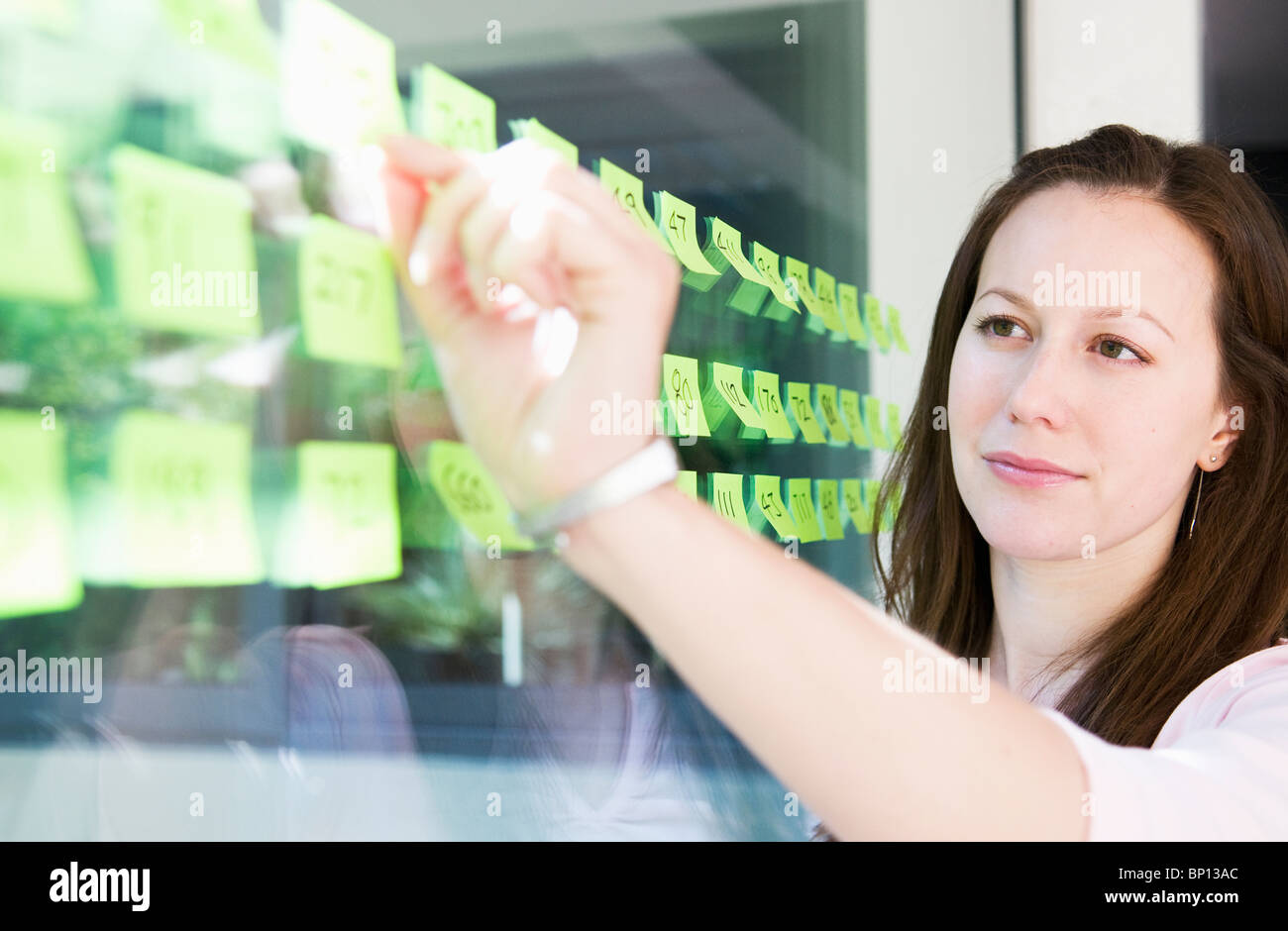 Women works with yellow labels - Stock Image