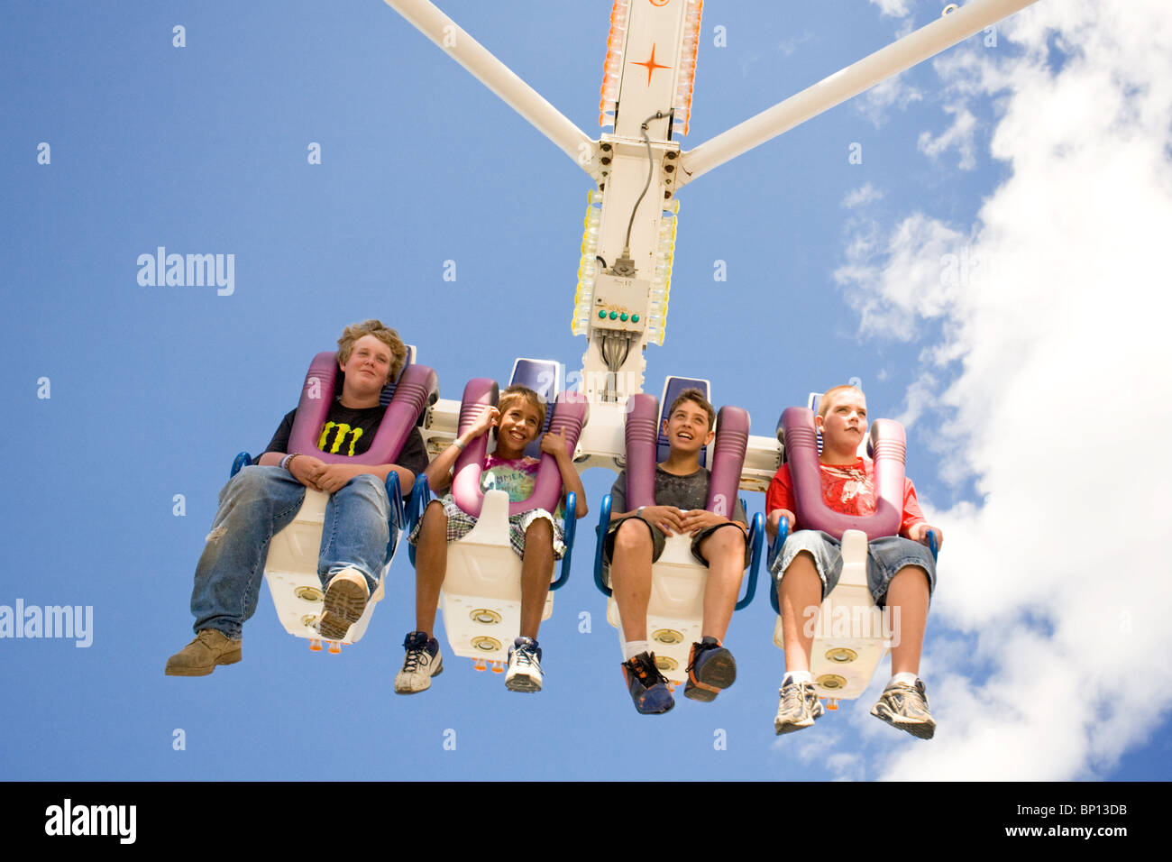 Four boys on a thrill ride at Cobleskill Sunshine Fair, New York State - Stock Image