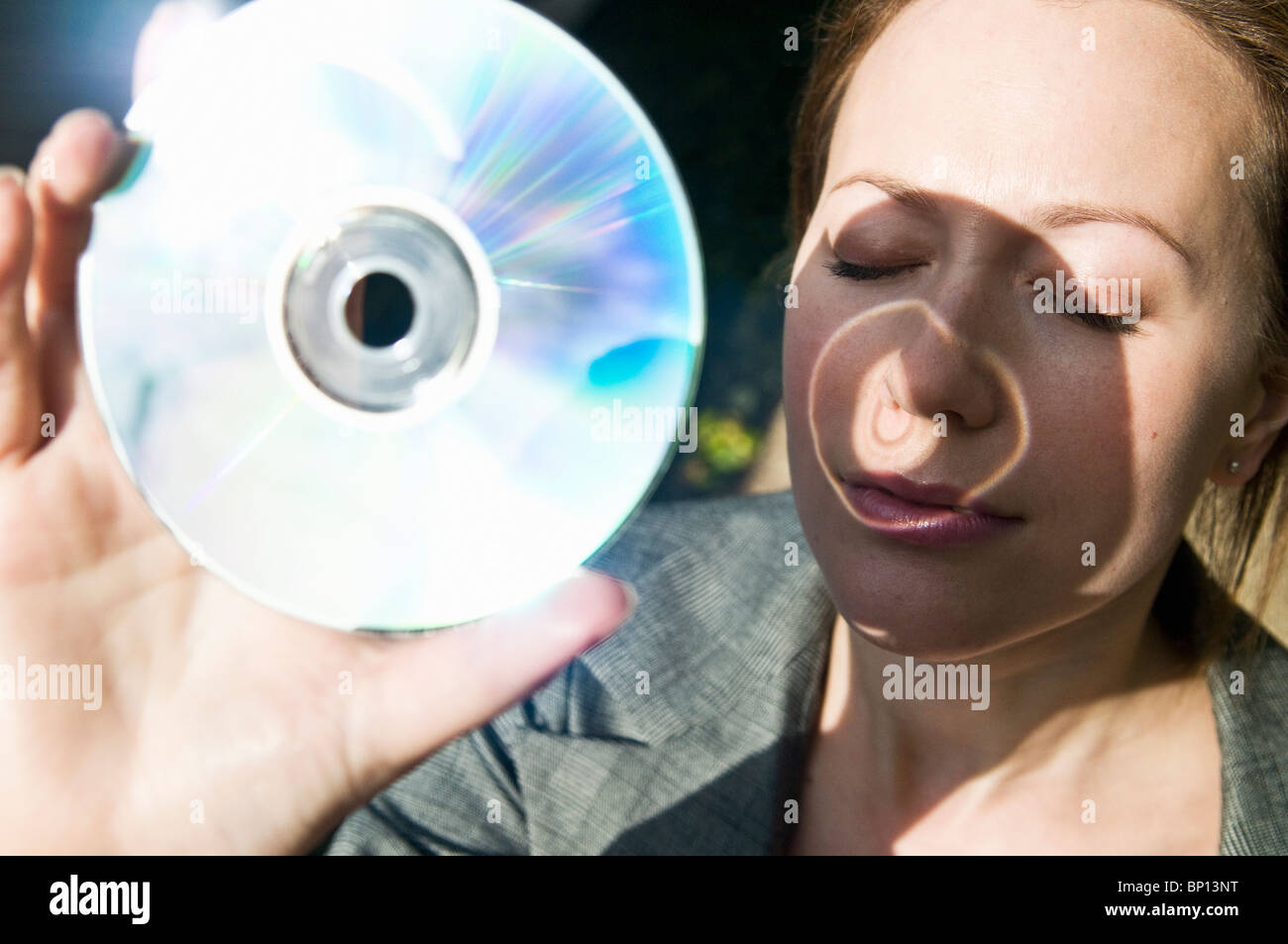 Woman holds DVD up to the sun - Stock Image