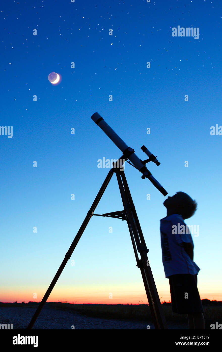 Little boy looking at moon with telescope - Stock Image