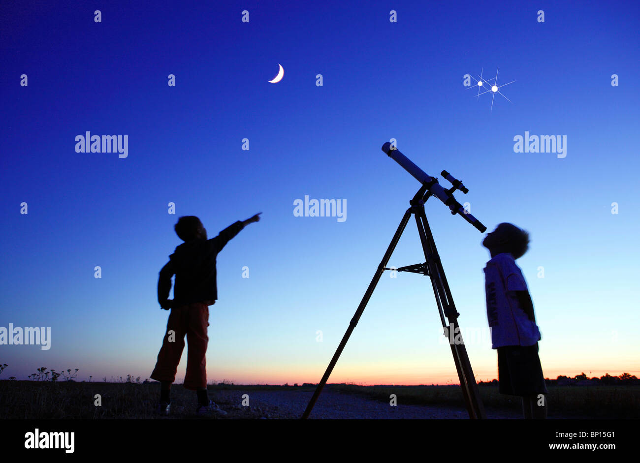 Little boys looking at moon with telescope - Stock Image