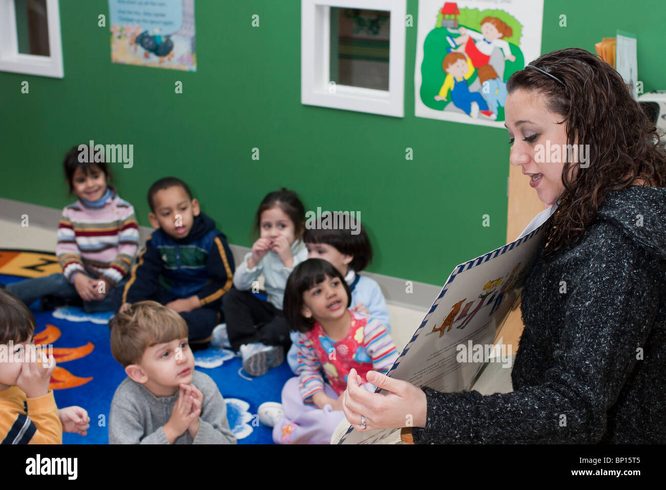 Preschool Classroom Teacher Reading A Book To Her Class While The Children Sit On