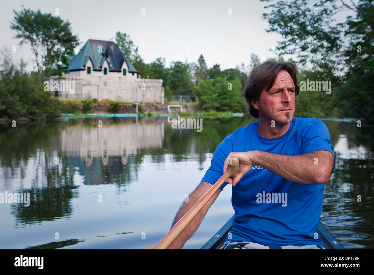 Huron native Jean Legare paddles a canoe on the riviere St-Charles river in the native reserve of Wendake - Stock Image