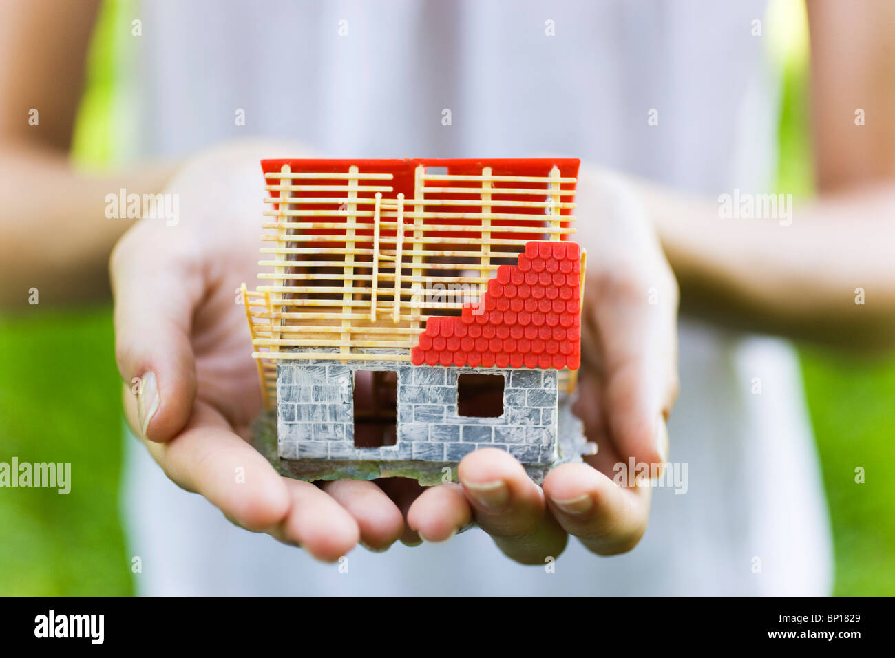 Young woman holding model house - Stock Image