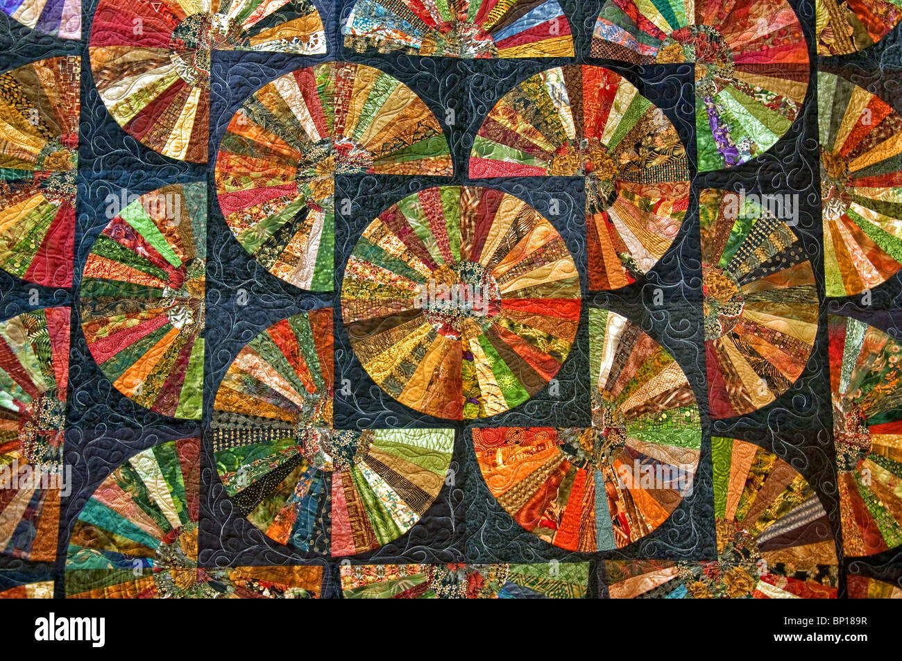 Black colorful quilt in many round shapes for a unique abstract pattern and texture design. Beautiful fabric artwork. - Stock Image