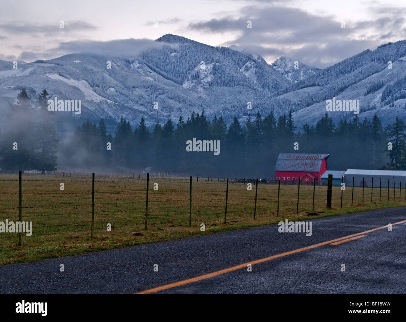 This Winter Country Farm Scene Has A Red Barn In The Background With Rural Lonely Road Snowy Mountains Backdrop