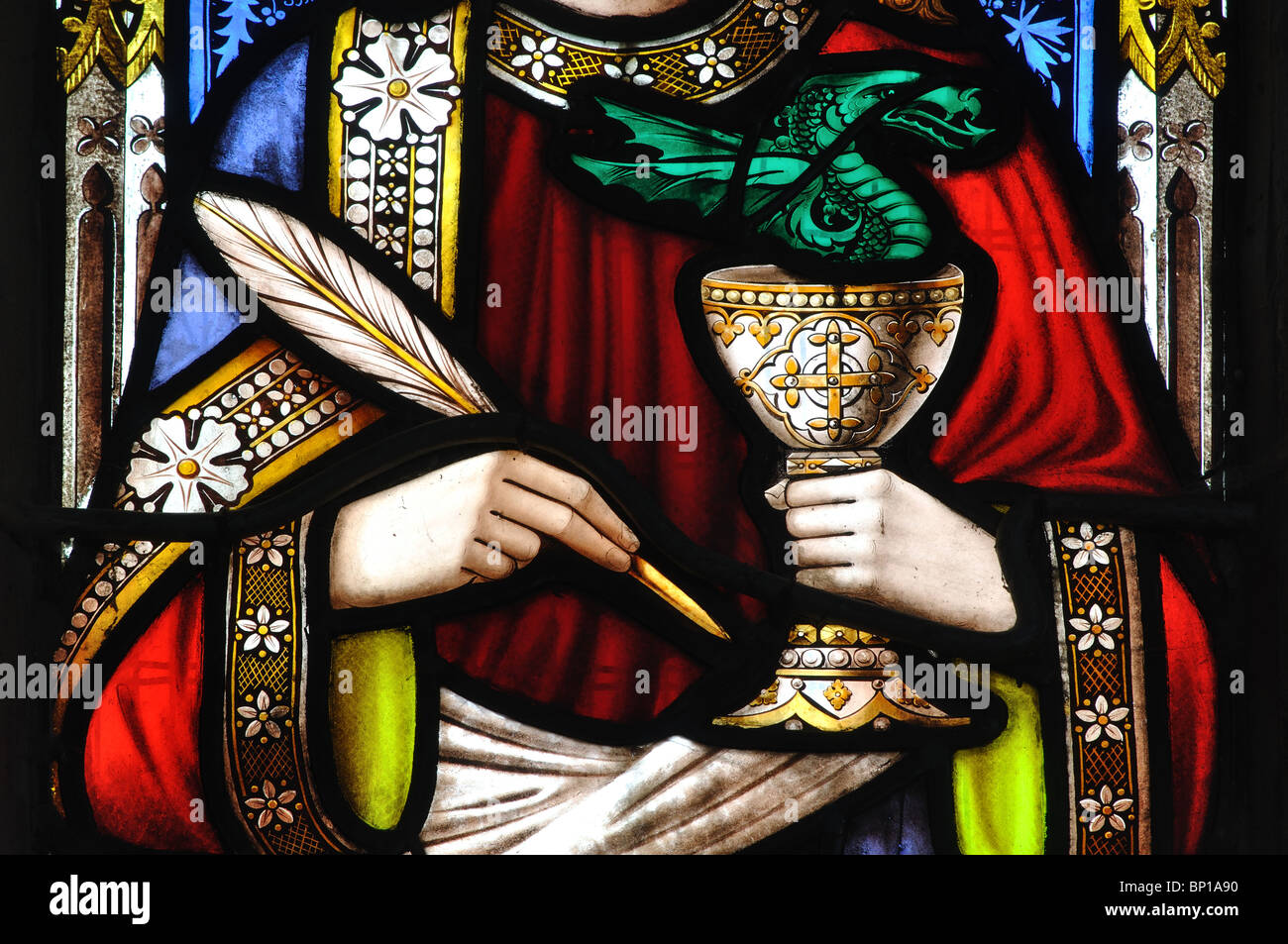 St. John with quill and chalice stained glass in St. Gregory`s Church, Tredington, Warwickshire, England, UK - Stock Image