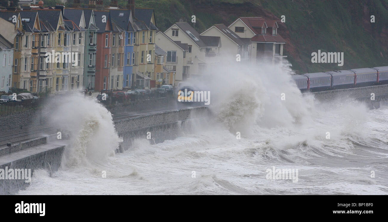 Huge waves crash over the sea wall and railway line at Dawlish in Devon. Picture by James Boardman - Stock Image