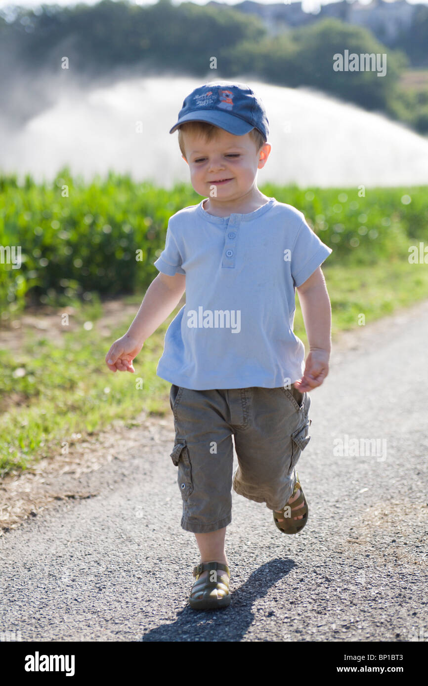 Little boy walking on country road Stock Photo - Alamy
