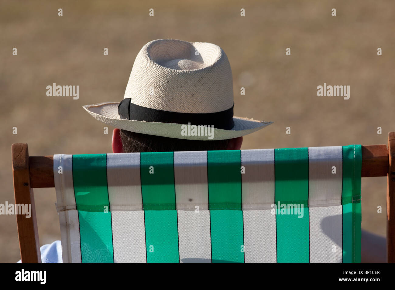 A man wearing a panama hat sits on a striped deck chair at Hyde Park, London. Photo:Jeff Gilbert - Stock Image