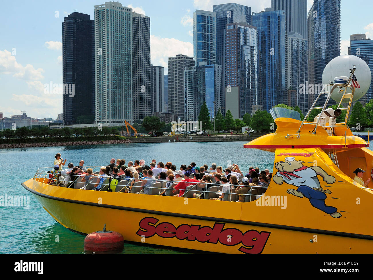 Excursion boat packed with tourists leaving Chicago's Navy Pier for a fast paced trip out onto Lake Michigan. - Stock Image