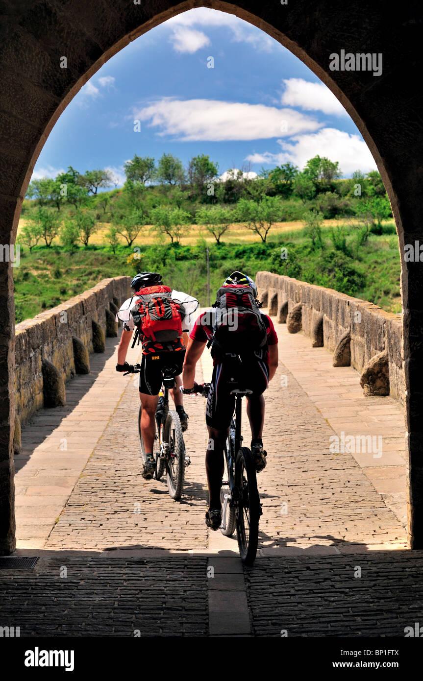 Spain, St. James Way: Biker at the medieval bridge of Puente la Reina - Stock Image